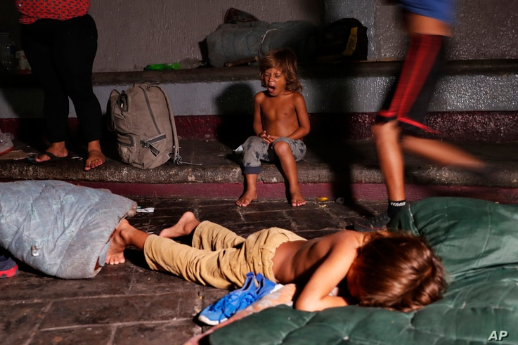 A child yawns after he is woken by Mexican immigration authorities who pushed camping migrant families from a park in Tapachula, Mexico, May 28, 2019. Authorities cleared the park and the makeshift encampment of Haitians and African migrants outside ...