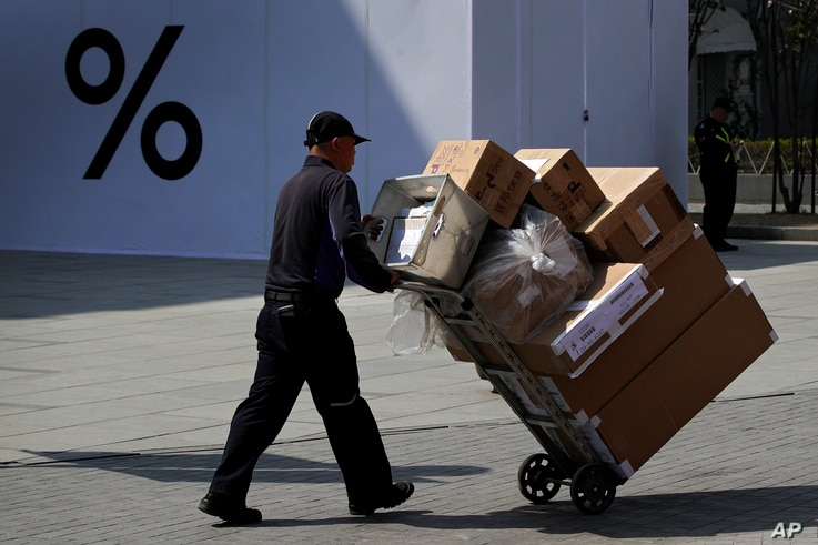 A delivery worker pushes boxes of goods at the capital city's popular shopping mall in Beijing, April 4, 2019. The U.S. and China opened a ninth round of talks Wednesday, aiming to further narrow differences in an ongoing trade war.
