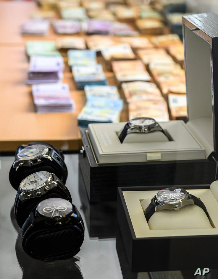 Banknotes and luxury watches are presented, May 3, 2019, at a press conference in Wiesbaden, Germany, about European and American investigators breaking up one of the world's largest online criminal trafficking operations.
