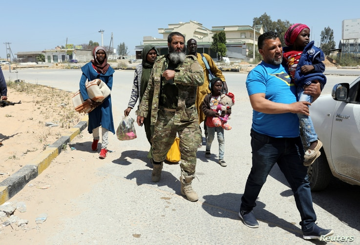 Members of Libyan internationally recognised government forces evacuate an African family during the fighting with Eastern forces, at Al-Swani area in Tripoli, Libya, April 18, 2019.