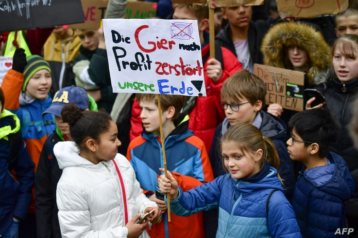 "FILE - Youths demonstrate with a banner reading ""the greed for profit destroys our earth!"" during the ""Fridays For Future"" movement on a global day of student protests aiming to spark world leaders into action on climate change on March 15, 2019 in B..."