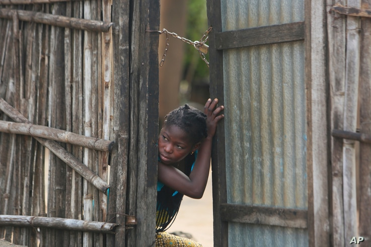 A young girl takes a look outside a gate near a site where two houses were crushed by the collapse of a massive, sprawling dumpsite in Pemba, Mozambique,  April, 29, 2019.
