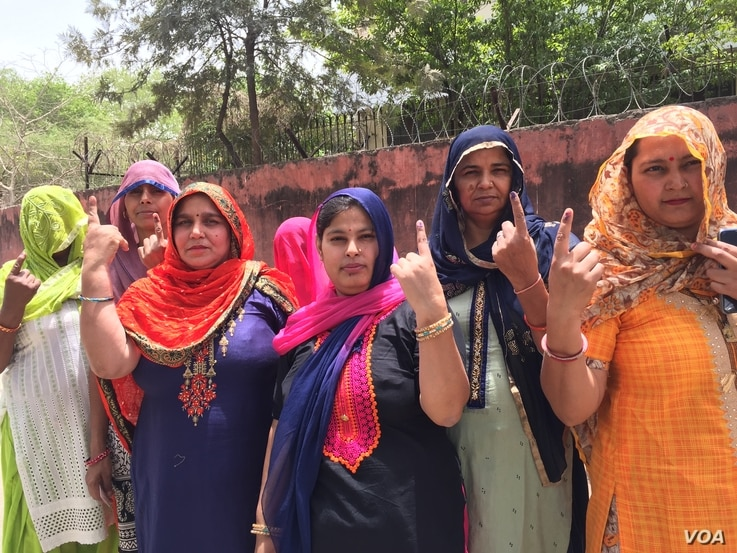 Women emerge from a polling booth in Haryana after casting their votes.