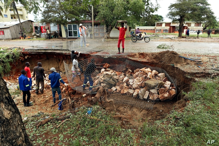 Men repair a road damaged by Cyclone Kenneth in Pemba city on the northeastern coast of Mozambique, April, 27, 2019.