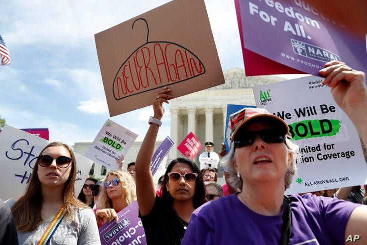 Gracie Burke, 19, center, a student at American University, joins other in a protest against abortion bans, May 21, 2019, outside the Supreme Court in Washington.