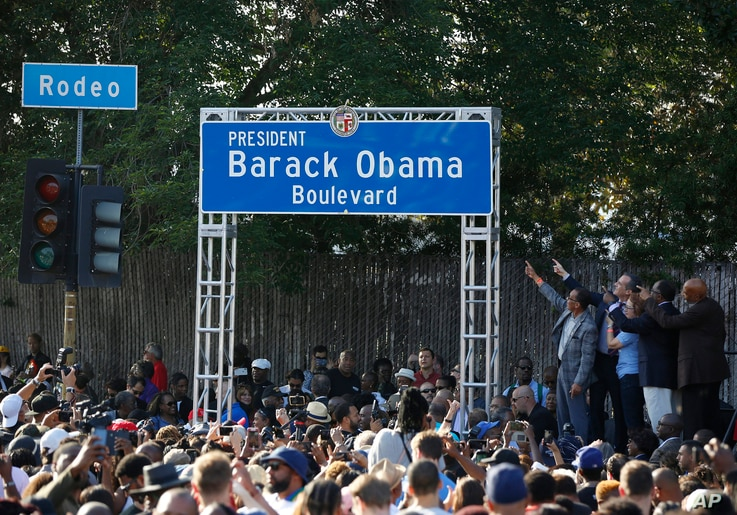 Los Angeles city officials at podium on right unveil the Obama Boulevard sign in Los Angeles, May 4, 2019. A stretch of road in Los Angeles was renamed after former President Barack Obama during a festival and unveiling ceremony.