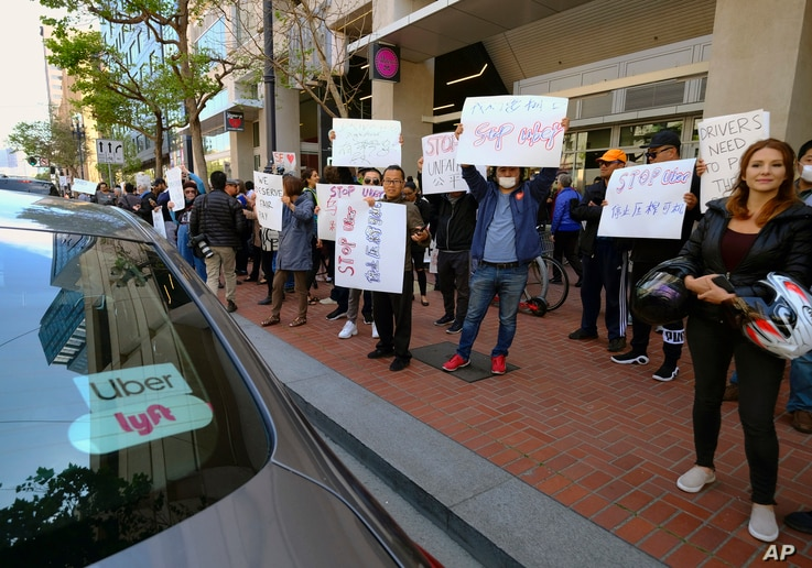Uber and Lyft drivers demonstrate outside of Uber headquarters, May 8, 2019, in San Francisco. As Uber executives lure investors to the largest technology IPO this year, the men and women behind the wheels are pushing for higher wages and recognition...