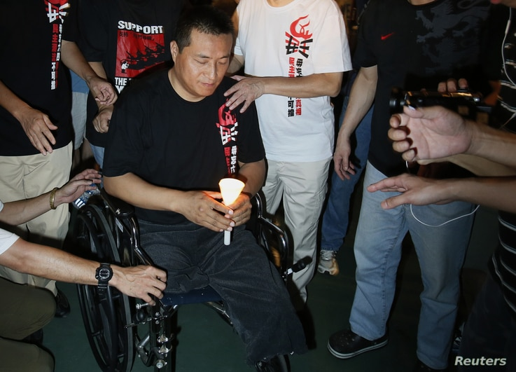 FILE - Fang Zheng, center, from mainland China takes part in a candlelight vigil at Hong Kong's Victoria Park, June 4, 2012, to commemorate those who died during the military crackdown of the pro-democracy movement at Beijing's Tiananmen Square, June...
