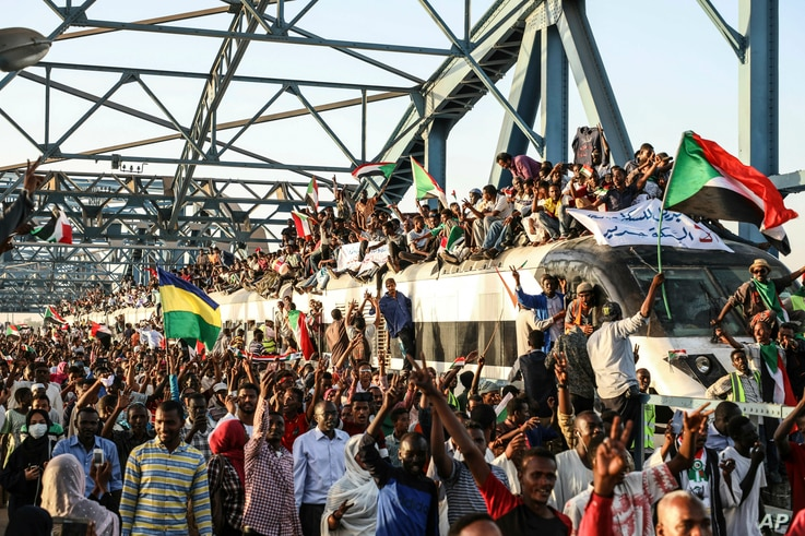 Sudanese protesters crowd a train in the capital Khartoum, April 23, 2019, demanding the military hand over power to a civilian body.