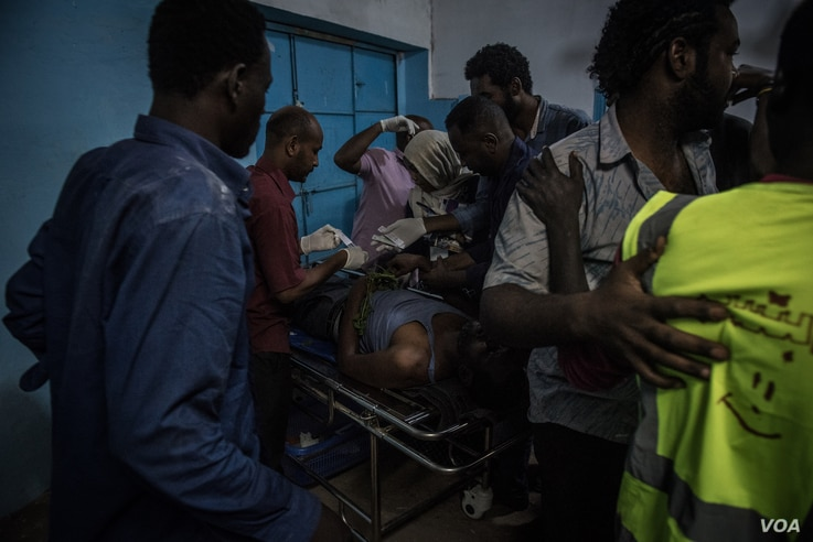 Medical staff attend to a man suffering convulsions from tear gas inhalation at a clinic in the sit-in in Khartoum on the night of May 13 2019. (J. Patinkin for VOA)