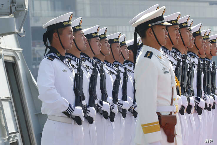 Chinese People's Liberation Army Navy troops stand in formation on the deck of a type 054A guided missile frigate 'Wuhu' as it docks at Manila's South Harbor for a four-day port call, Jan. 17, 2019 in Manila, Philippines. Two other ships from the Chinese Naval Task Group 'Handan,' also a guided missile frigate and Dongpinghu, a replenishment or supply ship, arrived with 'Wuhu' in the second such visit of a China People's Liberation Army Navy or PLAN, under President Rodrigo Duterte's administration.