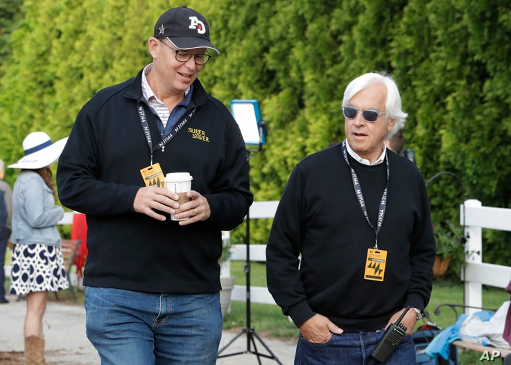 Improbable trainer Bob Baffert, right, and co-owner, Elliott Walden, walk to the track during training for Saturday's Preakness horse race at Pimlico race track in Baltimore, May 17, 2019.