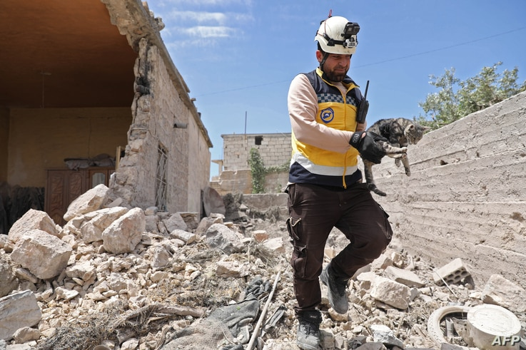 A member of the Syrian Civil Defense (White Helmets) caries a cat amidst rubble from a building damaged during reported shelling by government and allied forces, in the town of Hbeit in the southern countryside of the rebel-held Idlib province, May 3...