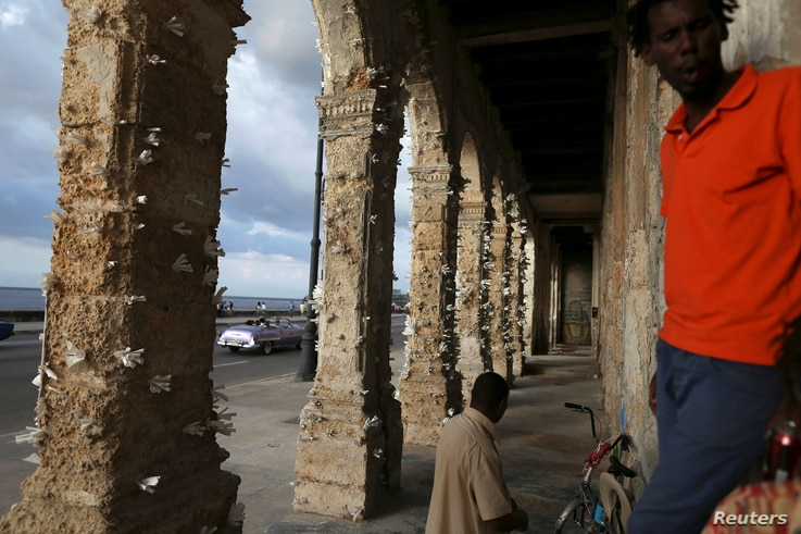 People stand near colonnades decorated with papers by Cuban artist Elio Jesus Fonseca, during the 13th Havana Biennial, in Havana, Cuba, April 12, 2019.