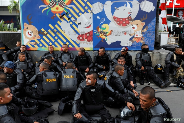 Police officers rest during a protest following the announcement of last month's election official results outside Indonesia's Election Supervisory Agency headquarters in Jakarta, Indonesia, May 22, 2019.