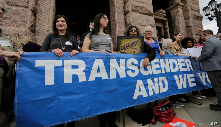 FILE - Members of the transgender community take part in a rally on the steps of the Texas Capitol, March 6, 2017, in Austin, Texas.