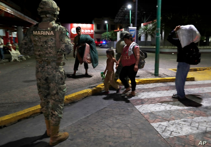 A Mexican marine stands by as camping migrant families are evicted from a park in Tapachula, Mexico, early May 29, 2019.