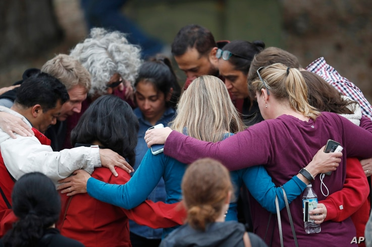 Parents gather in a circle to pray at a recreation center where students were reunited with their parents after a shooting at a suburban Denver middle school, May 7, 2019, in Highlands Ranch, Colo.