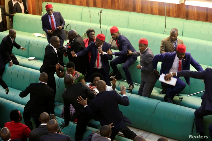 FILE - Ugandan opposition lawmakers fight with plain-clothes security personnel in the parliament while protesting a proposed age limit amendment bill debate to change the constitution for the extension of the president's rule, Kampala, Uganda, Sept....