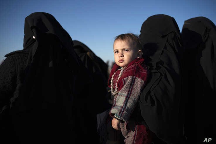 A woman holds a child as she waits to be screened by U.S.-backed Syrian Democratic Forces (SDF) after being evacuated out of the last territory held by Islamic State militants, in the desert outside Baghouz, Syria, Friday, March 1, 2019. (AP Photo/Felipe Dana)
