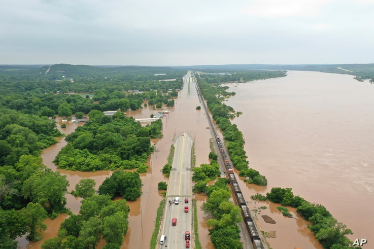 The Arkansas River spills over, flooding a highway in Sand Spring, Okla., May 28, 2019.