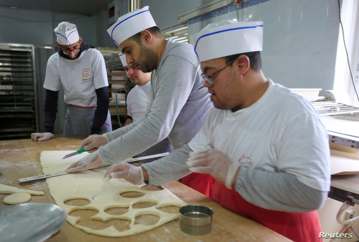 FILE - Ali Kerdi, 35, trains special needs students at a bakery in the southern city of Tyre, Lebanon, Dec. 18, 2018.