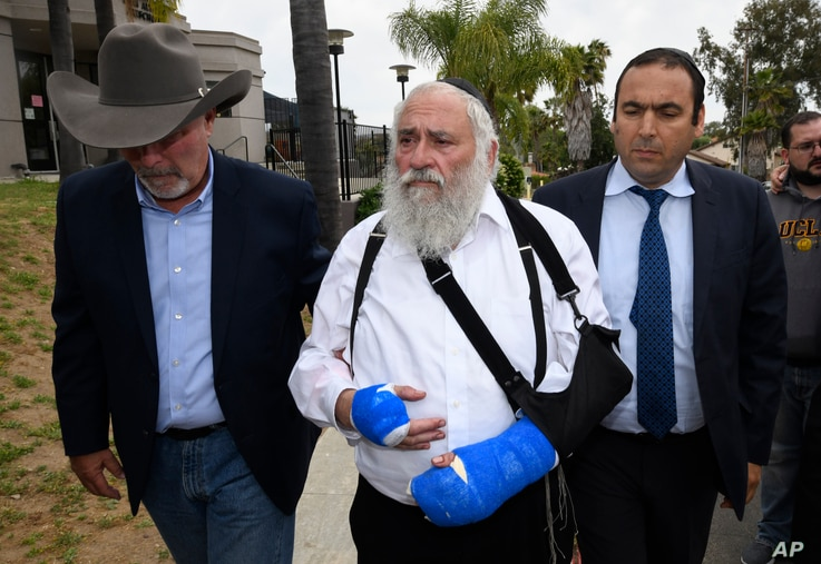 Rabbi Yisroel Goldstein, center, arrives for a news conference at the Chabad of Poway synagogue, April 28, 2019, in Poway, California.