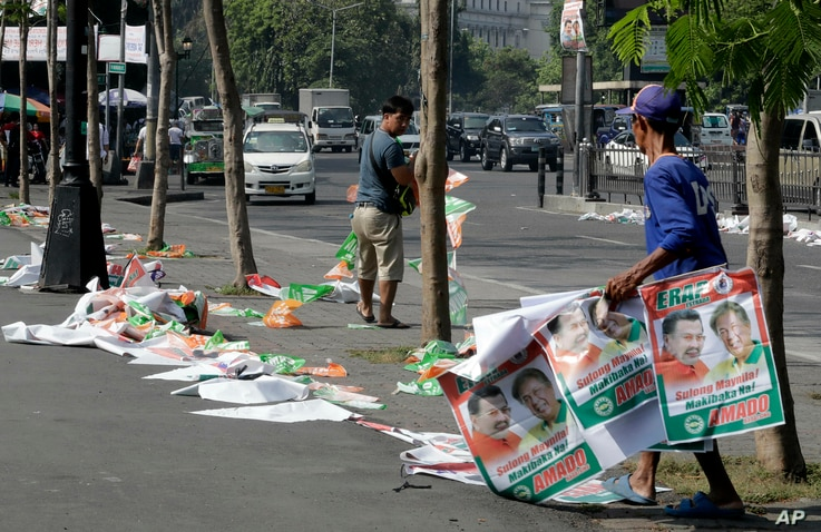 Manila City public workers remove the campaign posters around the Manila City Hall, a day after the country's midterm elections Tuesday, May 14, 2019 in Manila, Philippines.