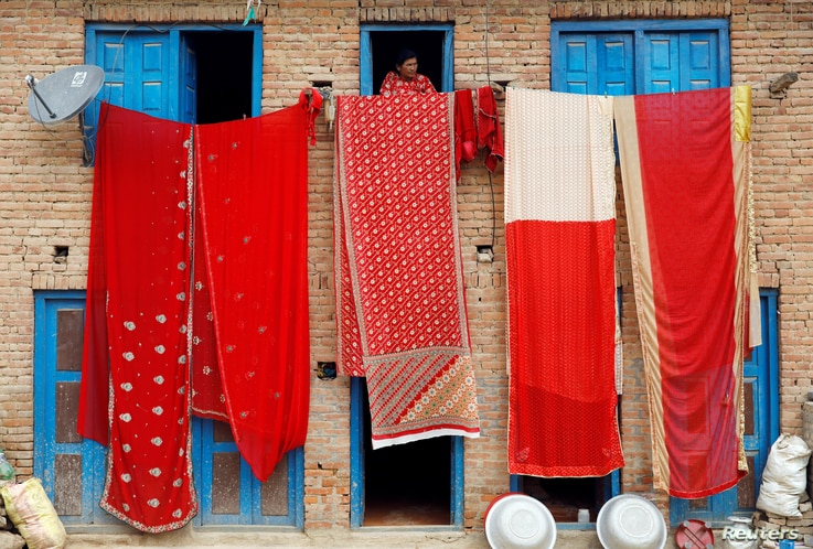 A woman looks out of the window of a house as saris, traditional clothing worn by women, are hanged out to dry in Lalitpur, Nepal April 17, 2019.