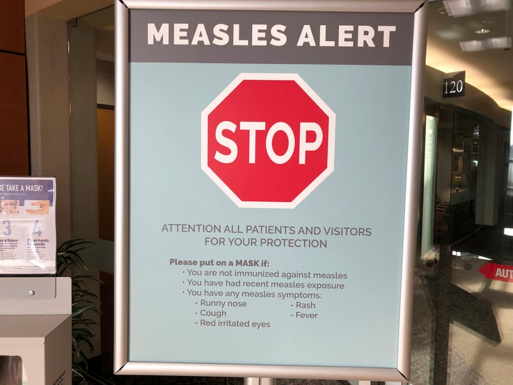 FILE - Signs posted at The Vancouver Clinic in Vancouver, Wash., Jan. 30, 2019, warn patients and visitors of a measles outbreak. A measles outbreak near Portland, Ore., has revived a bitter debate over personal belief exemptions to childhood vaccina...