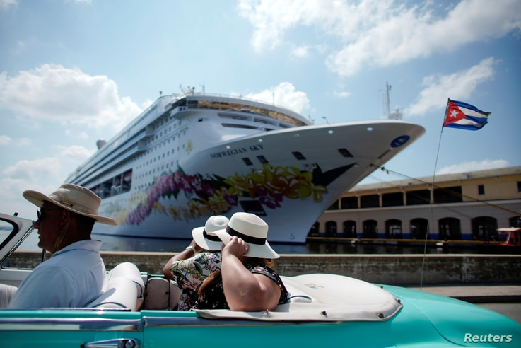 Tourists ride inside a vintage car as they pass by the Norwegian Sky cruise ship, operated by Norwegian Cruise Lines in Havana, Cuba, May 7, 2019.