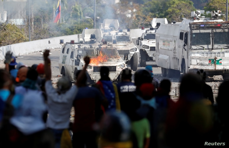 Opposition supporters react in front of a burning military vehicle during a rally against the government of Venezuela's President Nicolas Maduro in Caracas, Venezuela, May 1, 2019.