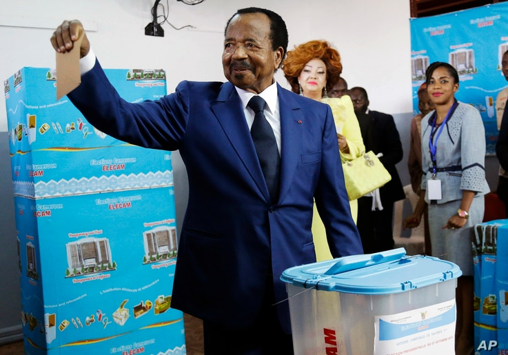 In this Sunday Oct. 7, 2018 file photo, Cameroon's Incumbent President Paul Biya, of the Cameroon People's Democratic Movement party, casts his vote during presidential elections in Yaounde, Cameroon. (AP Photo/Sunday Alamba, File)