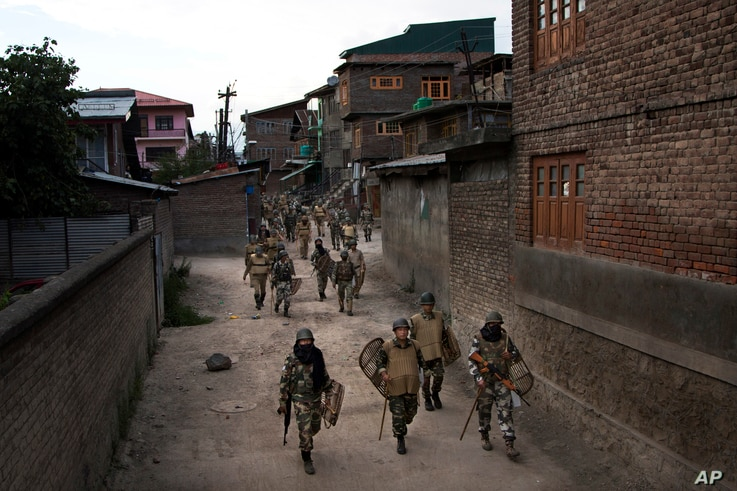In this Aug. 18, 2016 file photo, Indian paramilitary soldiers walk back towards their base camp after a day long curfew in Srinagar, Indian controlled Kashmir.
