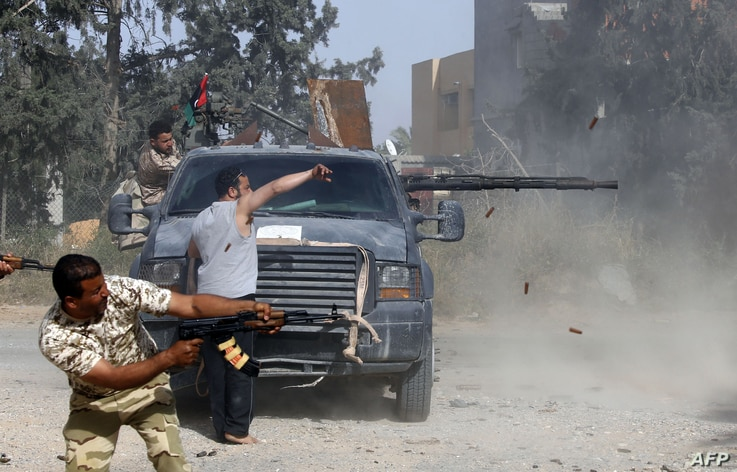 Libyan fighters loyal to the Government of National Accord (GNA)  fire their guns during clashes with forces loyal to strongman Khalifa Haftar south of the capital Tripoli's suburb of Ain Zara, on April 20, 2019.
