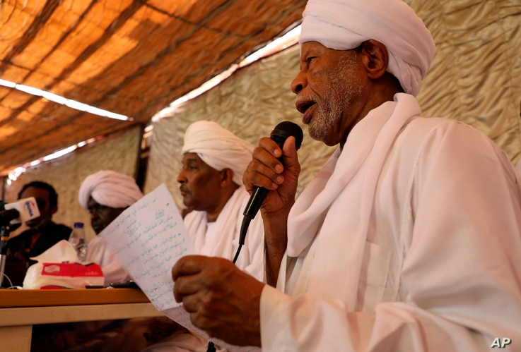FILE - Ibrahim al-Senoussi, a former aide to ousted President Omar al-Bashir, right, speaks at a press conference a day after a meeting of the Popular Congress Party, an Islamist party close to al-Bashir, was attacked by protesters, in Khartoum, Suda...