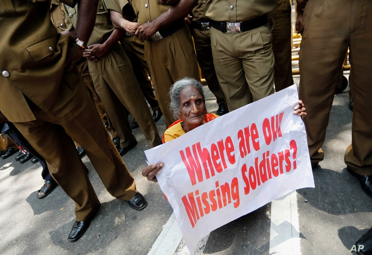 FILE - A Sri Lankan ethnic Tamil woman supporting the Dead and Missing Person's Parents Front holds a placard as police officers stand guard during a protest in Colombo, Sri Lanka, Aug. 30, 2013.