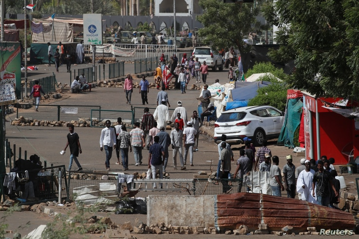 Sudanese protesters walk between barricades on a road leading to the defense ministry compound in Khartoum, April 30, 2019.