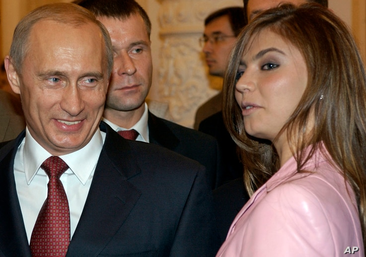 FILE - President Vladimir Putin, left, speaks with gymnast Alina Kabaeva at a Kremlin banquet in Moscow, Russia, Nov. 4, 2004.