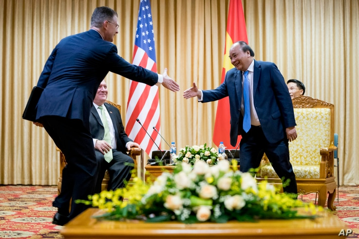 U.S. Ambassador to Vietnam Daniel Kritenbrink, left, shakes hands with Vietnamese Prime Minister Nguyen Xuan Phuc, right, as he meets with Secretary of State Mike Pompeo in Hanoi, Vietnam, Monday, July 9, 2018.