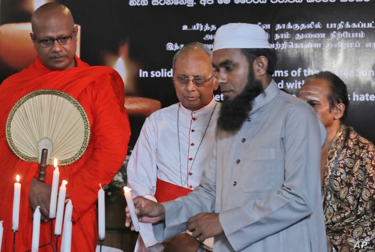 A Sri Lankan Muslim priest, lights a candle as Buddhist priest, left, Hindu priest, right, and Christian archbishop, center, watch during a function to express solidarity with all the victims of Easter Sunday attacks, in Colombo, Sri Lanka, April 28,...