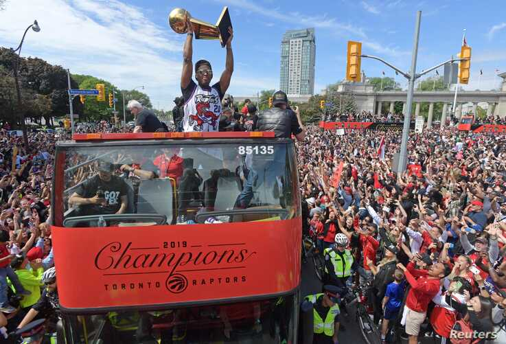 Toronto Raptors guard Kyle Lowry and teammates show off their trophy to fans during a parade through downtown Toronto to celebrate their NBA title, June 17, 2019.