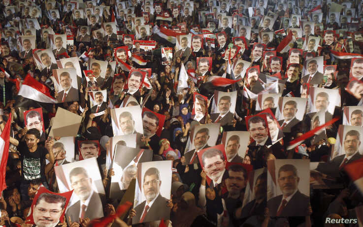 FILE - Members of the Muslim Brotherhood and supporters of Egypt's President Mohamed Mursi hold pictures of him as they react after the Egyptian army's statement was read out on state TV, at the Raba El-Adwyia mosque square in Cairo, July 3, 2013.