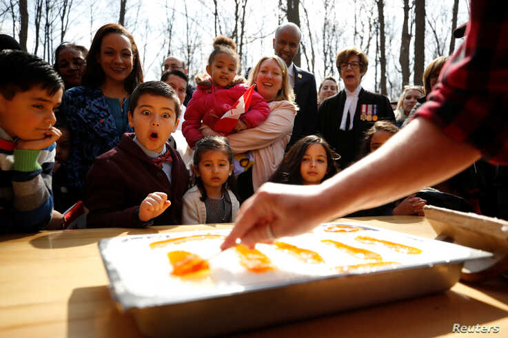 FILE - New Canadian citizen David Alfonso, 8, reacts as maple taffy is prepared for new Canadians following a citizenship ceremony at the Vanier Sugar Shack in Ottawa, Ontario, Canada, April 11, 2018.