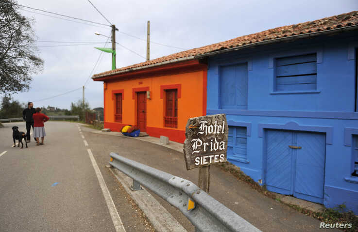 FILE - Villagers stand in front of decorated houses in the small village of Sietes, northern Spanish region of Asturias, Oct. 19, 2009.