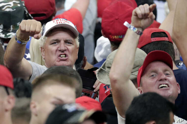 President Donald Trump supporters shake their fists at the media as Trump formally announced his 2020 re-election bid Tuesday, June 18, 2019, in Orlando, Fla