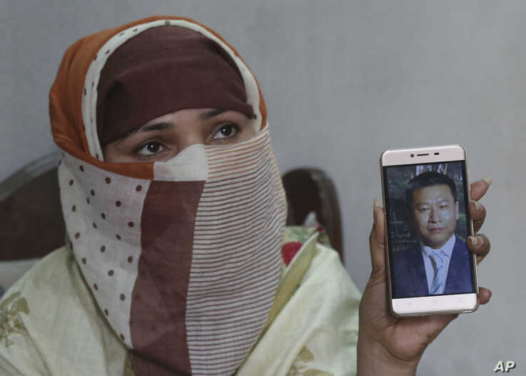 Sumaira, a Pakistani woman, shows a picture of her Chinese husband in Gujranwala, May 22, 2019.