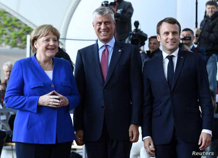 German Chancellor Angela Merkel, left, and French President Emmanuel Macron welcome Kosovo's President Hashim Thaci, center, to the Chancellery in Berlin, Germany, April 29, 2019.