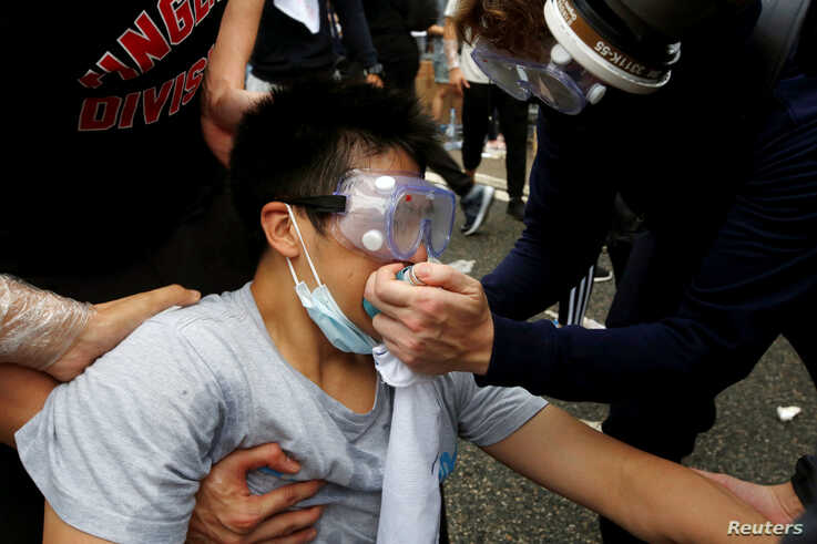 Protesters help a man during a demonstration against a proposed extradition bill where tear gas was fired, in Hong Kong, China June 12, 2019.