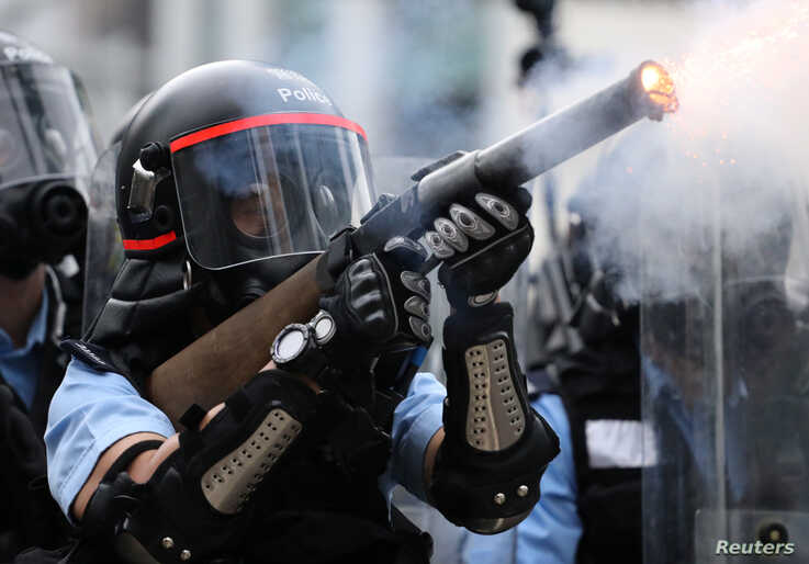 A police officer fires tear gas during a demonstration against a proposed extradition bill in Hong Kong, June 12, 2019.